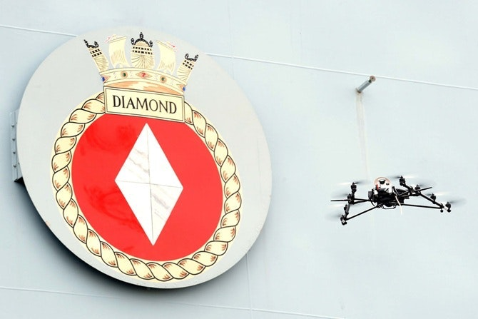 Drone flying in front of HMS Diamond nameplate