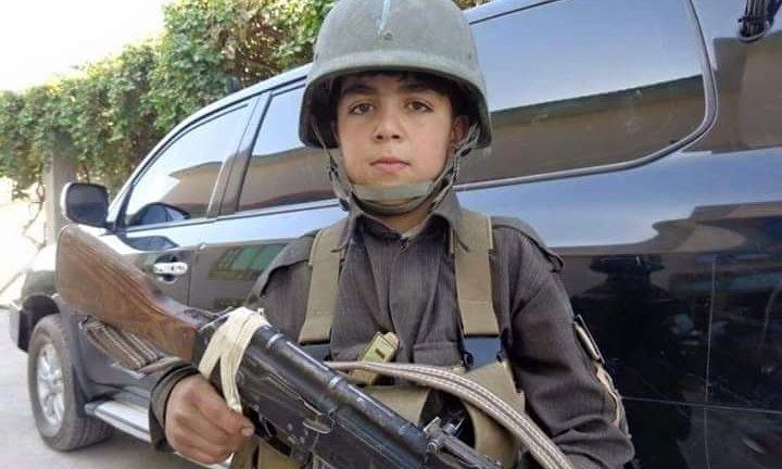 Child soldier Wasil Ahmad wearing a kevlar helmet and uniform