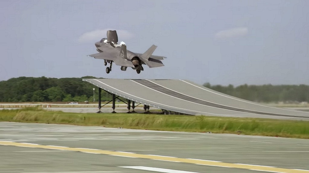 F-35B takes off from a ramp, flown by a British test pilot.
