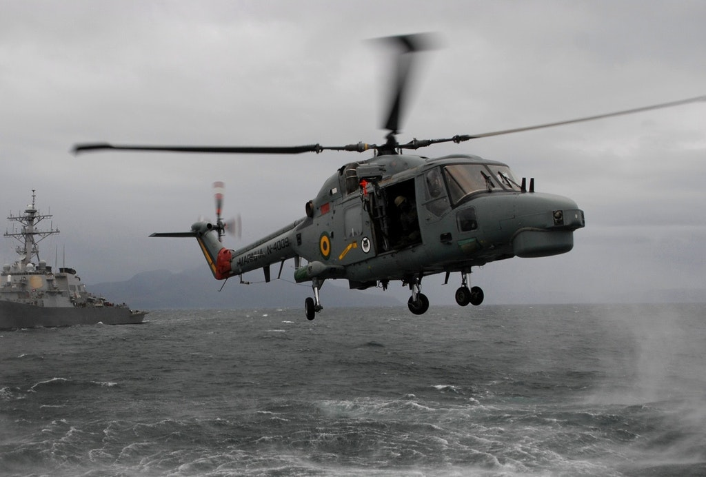 A Brazilian navy AH-11A Super Lynx Mk-21A helicopter prepares to drop a boarding team by fast rope during a visit, board, search and seizure exercise with the guided-missile destroyer USS Cole off the coast of Scotland.