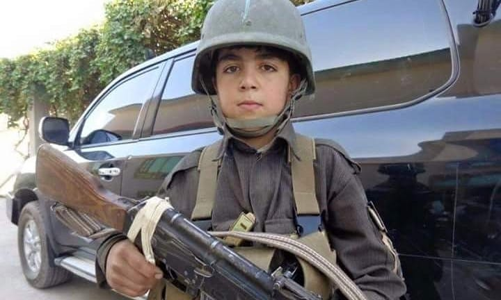 Child soldier Wasil Ahmad wearing a kevlar helmet and uniform